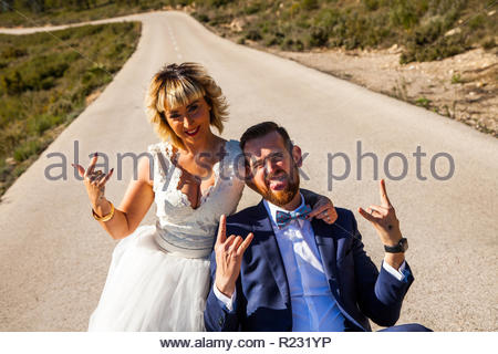 Couple of newlyweds pose in the middle of a lonely road making the horn gesture with their hands. - Stock Image