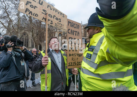 London, UK. 15th January 2019. A police officer asks a yellow-jacketed protester shouting at SODEM calling them traitors to move away. Groups against leaving the EU, including SODEM, Movement for Justice and In Limbo and Brexiteers Leave Means Leave and others protest opposite Parliament as Theresa May's Brexit deal was being debated.  While the two groups mainly kept apart, a small group, some in yellow jackets came to shout insults at pro-EU campaigners, while police tried to keep the two groups separate. Credit: Peter Marshall/Alamy Live News - Stock Image