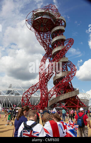 People sitting with Union Jack flags in front of Orbit sculpture tower designed by Anish Kapoor on a sunny day at - Stock Image