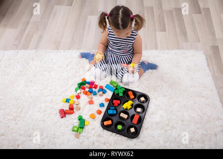 Elevated View Of Girl Sitting On Carpet Playing With Colorful Blocks At Home - Stock Image