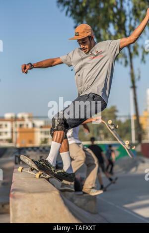 A skateboarder preforming a trick in a skatepark. - Stock Image