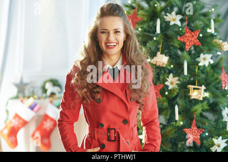 Portrait of happy young woman in red trench coat near Christmas tree - Stock Image