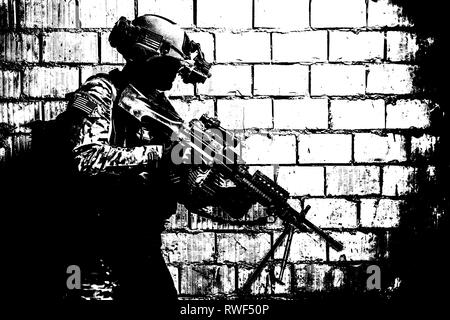U.S. Army Ranger with machine gun and night vision goggles, moving along the wall. - Stock Image
