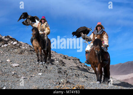 Kazakh brothers out hunting in the Altai Mountains of western Mongolia riding on their horses with their golden - Stock Image