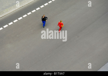 man woman pass eachother aerial view road tarmac berlin germany deutschland red blue space - Stock Image