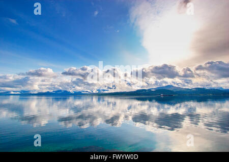 Mountains are reflected in Ofotfjorden near Evenes in  northern Norway. - Stock Image