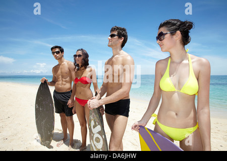 Friends posing with surboards. - Stock Image