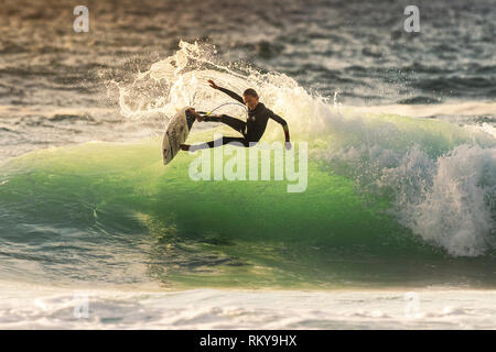 A young surfer riding a wave at Fistral in Newquay in Cornwall. - Stock Image