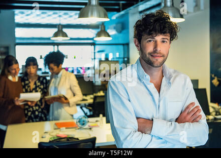 Businessman standing in office - Stock Image