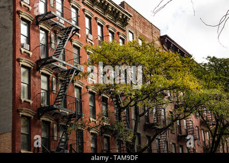Close-up view of New York City style apartment buildings with emergency stairs along Mott Street in Chinatown neighborhood of Manhattan, New York, USA - Stock Image