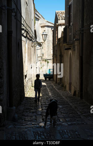Street scene of boy and dog in cobble stones alleyway in Erice, Sicily, Italy - Stock Image