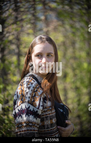 A young woman standing in green park. Mid shot - Stock Image