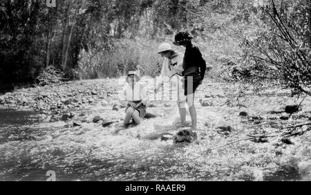 Three young women hike up their skirts and frolic in a stream, ca. 1925. - Stock Image