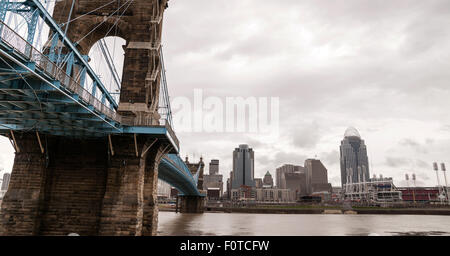 The Ohio River is at flood stage as it passes underneath a historical suspension bridge - Stock Image