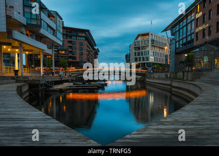 Aker Brygge Oslo, view at dusk of the harbour inlet inside the newly developed area of the Aker Brygge harbour district in Oslo, Norway. - Stock Image