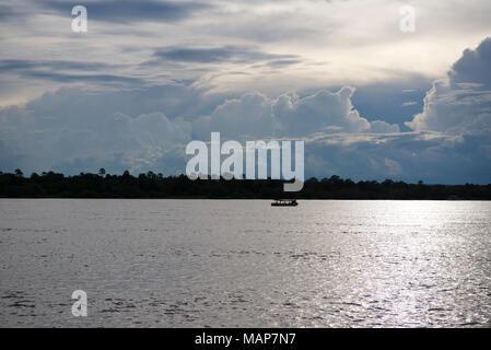 A boat motors down the Zambezi River, Zimbabwe Zambia border as Cumulo Nimbus rain clouds form in the background, at sunset - Stock Image