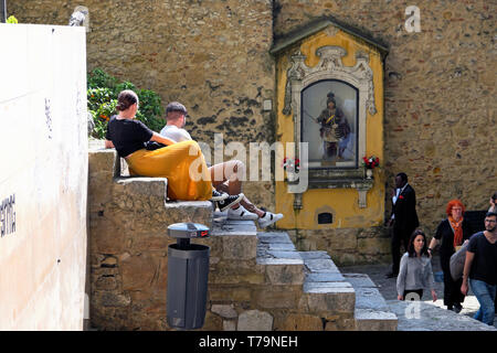 Tourists sitting on steps by the statue of St George shrine at entrance Castelo de Sao Jorge Lisbon Castle in Lisbon Portugal Europe EU  KATHY DEWITT - Stock Image