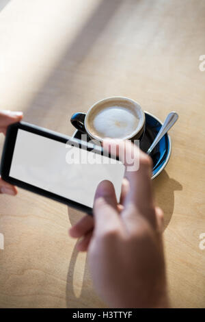 Female hands photographing a coffee cup - Stock Image
