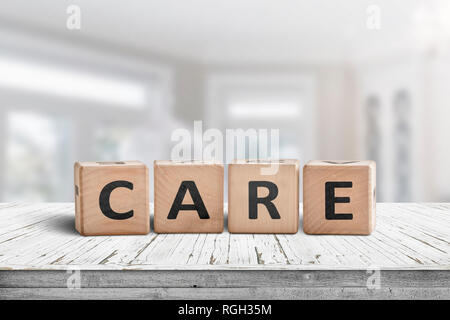 Care sign on a white table in a bright room with a blurry background - Stock Image