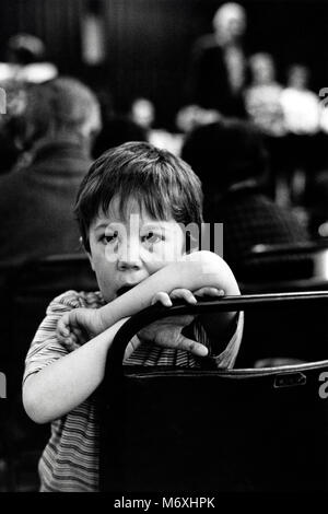 Boy posing in audience at small eisteddfod in village hall at Y Groeslon Gwynedd North Wales UK - Stock Image