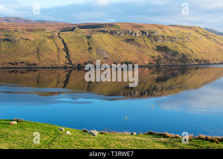 Colourful reflections in the calm water of Loch Harport on Isle of Skye, Highland Region, Scotland, UK - Stock Image