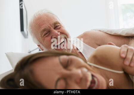 Playful, affectionate senior couple in bed - Stock Image