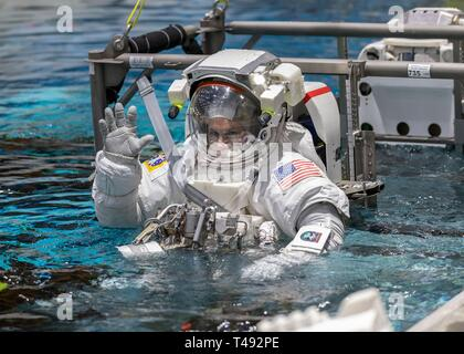 Boeing Commercial Crew Program astronaut Josh Cassada waves before entering the pool at the Neutral Buoyancy Laboratory for ISS EVA training in preparation for future spacewalks while onboard the International Space Station at the Johnson Space Center April 12, 2019 in Houston, Texas. - Stock Image