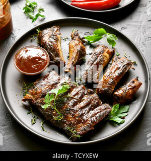 Close up of grilled spare ribs on plate over black stone background. Tasty bbq meat. - Stock Image