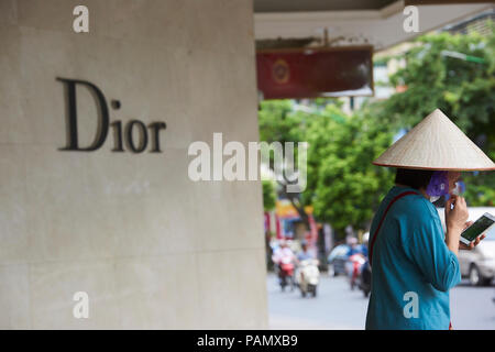 A woman wearing a traditional Vietnamese conical hat made of straw stands outside a Dior Shop in Hanoi, Vietnam. - Stock Image