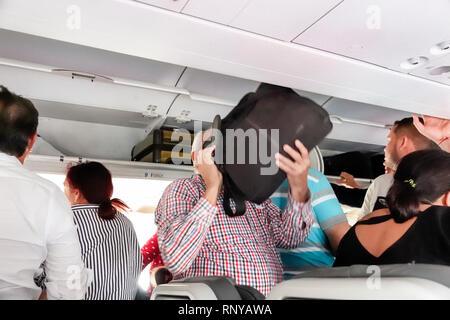 Cartagena Colombia Aeropuerto Internacional Rafael Nunez Airport Avianca Airlines arriving passengers Hispanic onboard inside aircraft cabin overhead - Stock Image