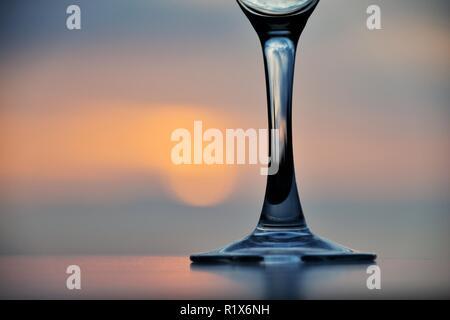 Stem of wine glass at sunset - Stock Image