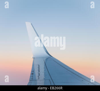 View of the wing of a passenger jet at sunset - Stock Image
