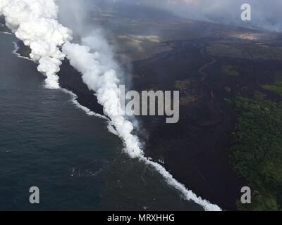 Lava and poisonous sulfur dioxide plumes rise as molten magma reaches the ocean from the eruption of the Kilauea volcano May 25, 2018 in Pahoa, Hawaii. Hot lava entering the ocean creates a dense white plume called 'laze' (short for 'lava haze'). Laze is formed as hot lava boils seawater to dryness. The process leads to a series of chemical reactions that create a billowing white cloud composed of a condensed seawater steam, hydrochloric acid gas, and tiny shards of volcanic glass. The cloud is as corrosive as dilute battery acid, and should be avoided. - Stock Image