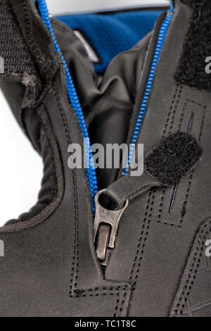 Detail of the zipper of a motorcycle boot isolated on white. - Stock Image
