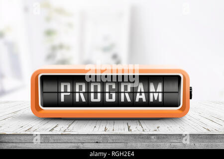 Program message on a retro clock in orange on a wooden table in bright light - Stock Image