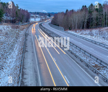 Early morning commuter traffic through frosty landscape long exposure with headlight light trails - Stock Image