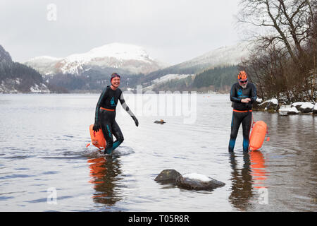 Open water swimmers in the freezing cold water of fresh water Loch Lubnaig, Callander, Loch Lomond and the Trossachs National Park, Scotland, UK - Stock Image
