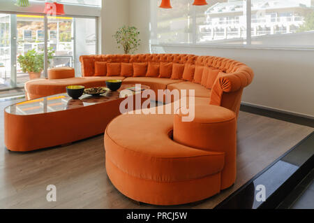 Orange curved sofa and table in a large, modern, contemporary room. - Stock Image