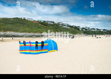 A colourful windbreak and shelter on Crantock Beach in Newquay in Cornwall. - Stock Image