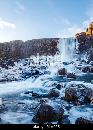 Frozen water on the rocks around the base of a waterfall in Thingvellir in central Iceland - Stock Image