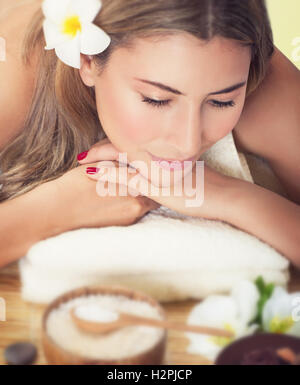 Closeup portrait of a beautiful woman at spa salon, lying down on the massage table, health care and beauty treatment - Stock Image
