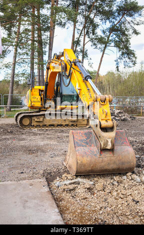 Yellow caterpillar tracked JCB JS130 LC heavy plant digger tracked excavator with bucket scoop at RHS Gardens, Wisley, Surrey, UK - Stock Image