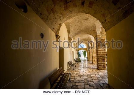 A exterior hallway of arches in the ancient port city of Brindisi, Italy, in the Southern Puglia Region - Stock Image