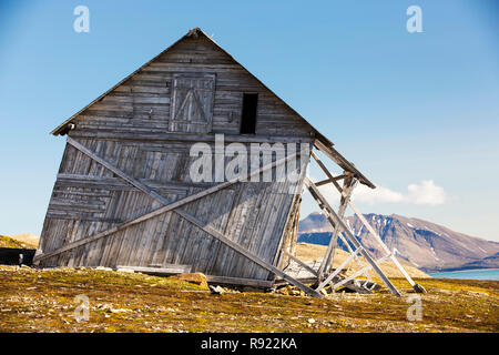 An old house at Recherchefjorden (77Âáẁž31Ãḃ™n 14Âáẁž36Ãḃ™e), Van Keulenfjorden, Spitsbergen, Svalbard. It is gradually sliding down slope due to solifluction and permafrost melt. Climate change is accelerating permafrost melt and causing huge damage across the Arctic. It is also one of the feedback loops that exascerbate climate change, as the permafrost locks away billions of tonnes of methane (a greenhouse gas 23 times more potent than C02), as the permafrost melts this methane is released into the atmosphere with porentially disastrous consequences. - Stock Image