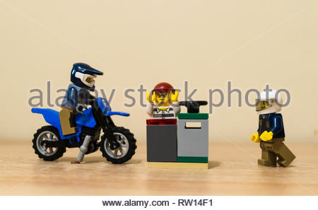 Poznan, Poland - February 27, 2019: Policeman on a motorcycle and by feed approaching a escaped prisoner trying to open a safe. - Stock Image