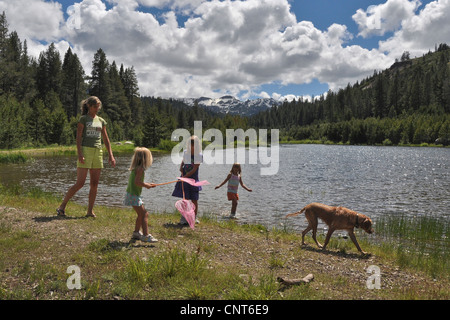 parent mom kids young girls butterfly butterflies snakes mountain lake - Stock Image