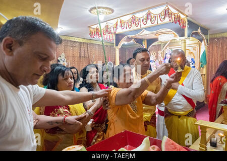 Surrounded by family, a Hindu woman in her late seventies offers fire to the deities as an act of appreciation. In Ozone Park, Queens, NYC. - Stock Image