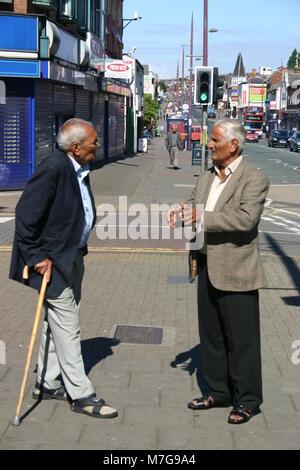 Two elderly Asian men talking on the street, Soho Road, Birmingham - Stock Image