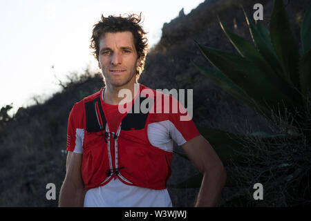 A strong, fit and athletic middle aged looks straight at the camera as the fading sun back lights him in the mountains surrounding the town of El Aren - Stock Image