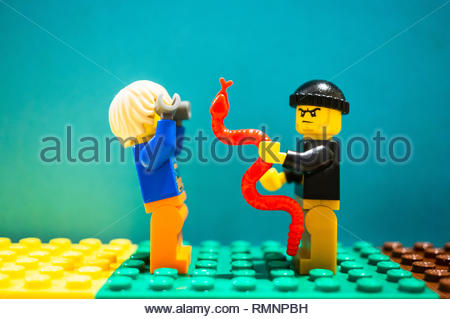 Poznan, Poland - February 13, 2019: Lego thief with angry face holding a snake and scaring an man holding his hands up. - Stock Image